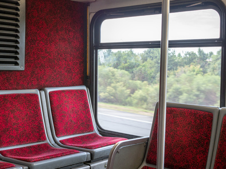 Red seats in back of commuter bus moving on high way Stock Photo