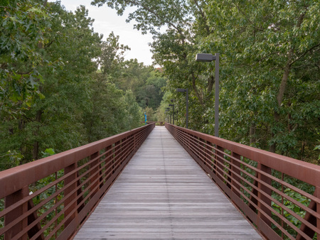 Wooden footpath with rusty steel guard rails in wood area