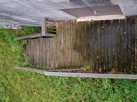 Overhead shot of wooden walkway leading to rusty door in suspicious wooded area
