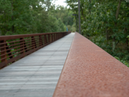 Close view of rusted hand rail along a wooden foot bridge