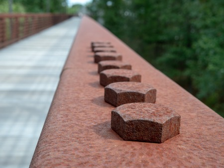 Row of hex screws in a rusted steel handrail on a wooden bridge on hiking path Stock Photo