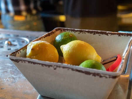 Lemons and limes with peeler sitting in bowl of a bar for bartenders to make cocktails
