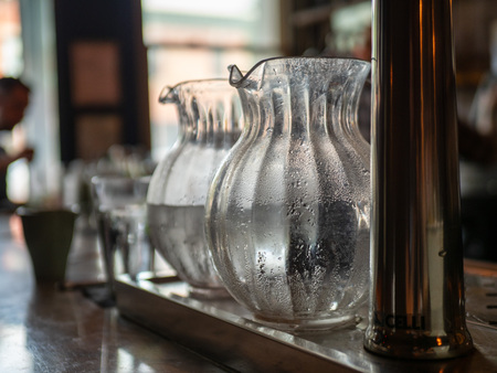 Two glass water pitchers with condensation sitting on bar counter