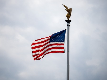 American flag blowing on overcast day with eagle statue over head