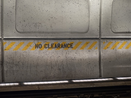 No clearance sign painted on a concrete wall in subway station