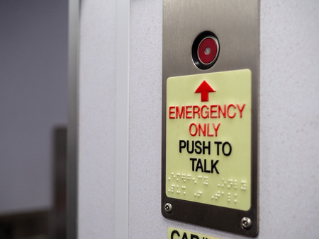 Red button with emergency only push to talk text with braille Stock Photo