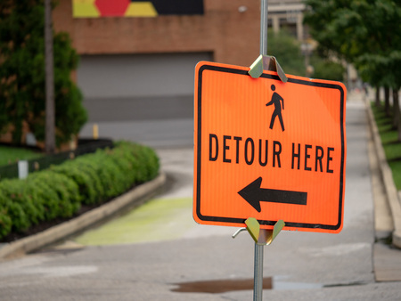 Detour here sign with person walking symbol and arrow pointing left