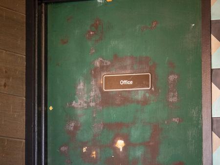 Green door office door card with paint stripping and rundown