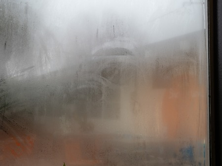 Window in store covered in fog and condensation from the indoors