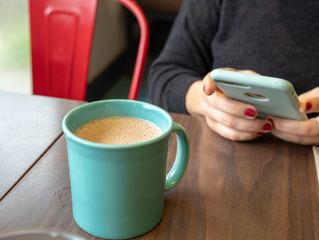 Woman using phone while waiting for hot chocolate to cool in teal cup
