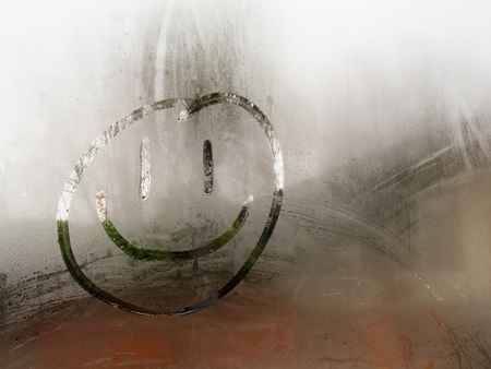 Cartoon happy smiley face drawn on a condensation covered window during the day time 写真素材