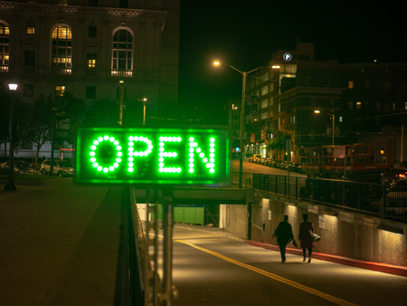 Green lighted open sign in dark city area with people walking in to tunnel