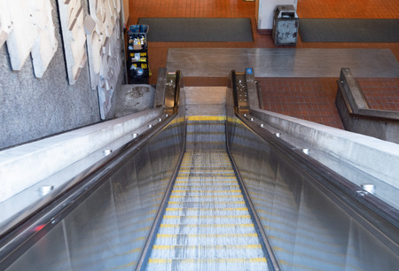 Escalator leading down into a subway tunnel in the daytime
