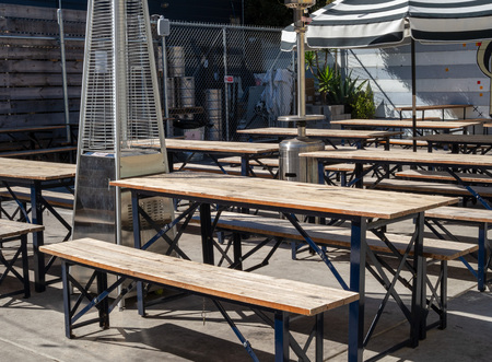 Outdoor picnic tables and umbrellas in an outdoor restaurant brewery dining area during sunny day Stock Photo