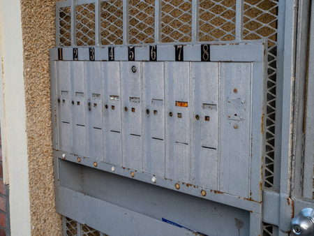 Outdoor apartment mailboxes with rusty look and dirty state units 1 to 8