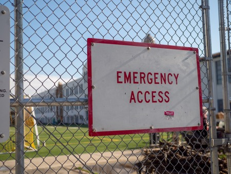 Emergency access sign posted on chain-link fence guarding a school sports area