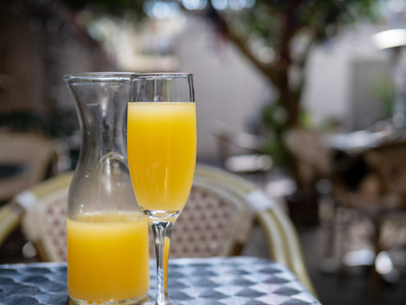 Orange juice mimosa drink in glass and carafe for brunch outdoors