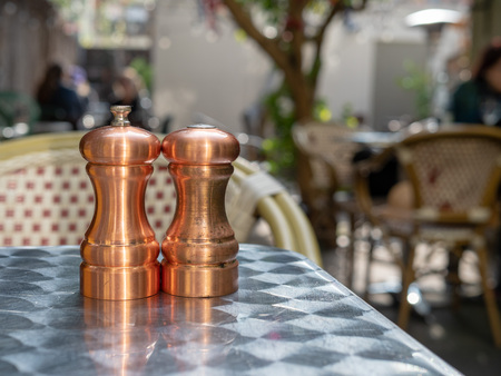 Cooper salt and pepper shakers and grinders sitting outdoors on  restaurant table