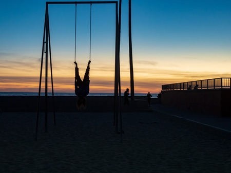 Man hanging upside down on gymnastic rings outdoors in the dusk sky on a beach