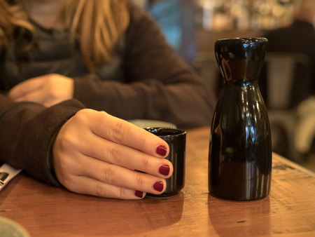 Woman with painted finger nails holding a sake glass next to black bottle in restaurant
