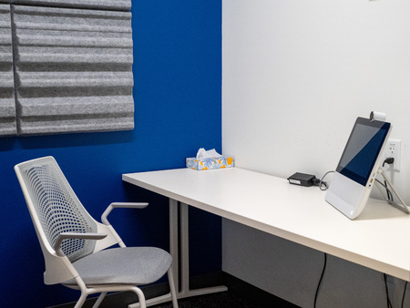 Bright, private office conference room with monitor and teleconference camera