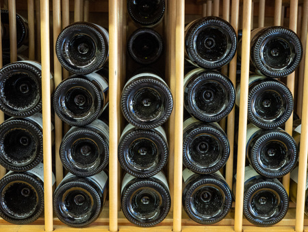 Bottles of red wine in layers in wine rack with ends with bottoms shown in display Imagens