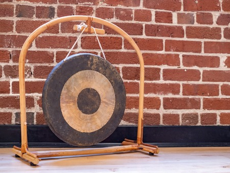 Small suspended gong sitting on wooden floor against brick wall backdrop Stok Fotoğraf