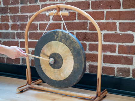 Small suspended gong sitting hit with mallet by hand of a woman