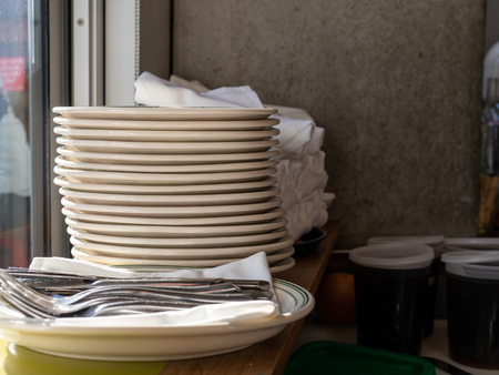Stack of plates and utensils and containers of sauces