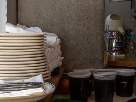 Plates, utensils, napkins, drink mix materials behind bar