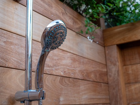 Handheld steel showerhead hanging outside within wooden fence area and trees