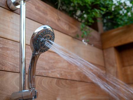Water steams flowing out of handheld shower head in outdoor shower Reklamní fotografie
