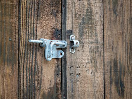 Steel rusty metal latch lock hanging outdoors on wooden double door