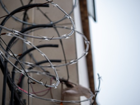 Close view of barbed wire razor wire on top of fence outside of a building in overcast