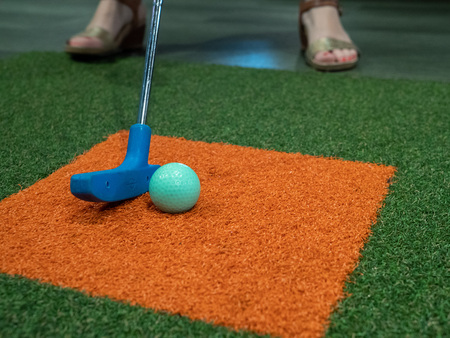 Blue putter on turf next to green golf ball on miniature golf course with woman hitting Stock Photo