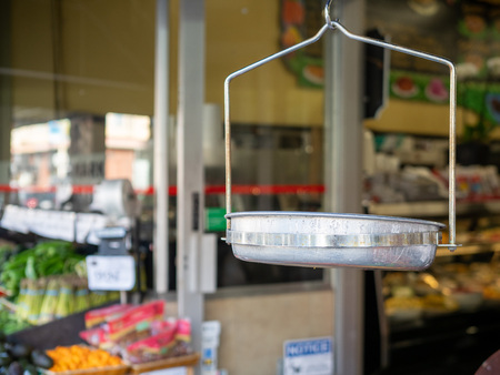 Hanging steel grocery scale at the entrance of a supermarket with produce Imagens