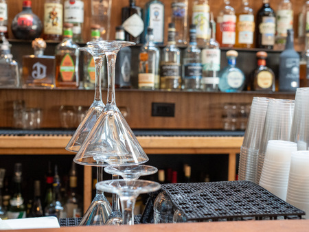 Martini glasses stacked behind a busy bar with plastic cups and liquor Reklamní fotografie - 124758519