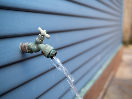 Water streaming out of outdoor faucet for garden hose outdoors