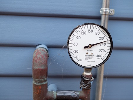 Water pressure gauge manometer with cobwebs and rusty pipes and tape outside of home. Lack of care Imagens