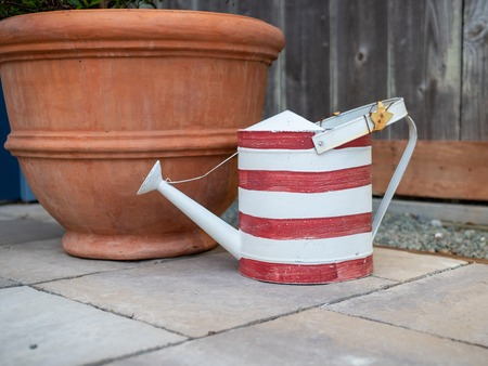 Red and white stripped watering can siting next to large flower pot on concrete behind fence
