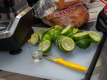 Squeezed lime, shot glass and knife sitting on small cutting board, making margaritas for party