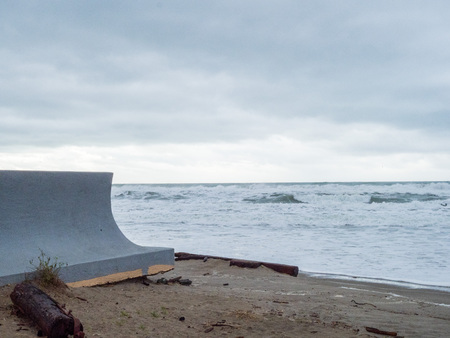 Concrete seawall protecting property from waves from an ominous storm in distance