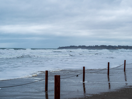 Makeshift fence of wooden posts and strings on a storm beach with waves coming on shore