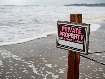 Private property no trespassing sign on pole and wire fence on beach property next to waves