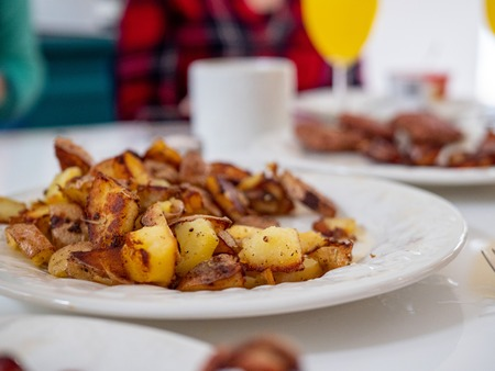 Close up of traditional American breakfast plate of potatoes, sausage, bacon on a dining table with full breakfast spread