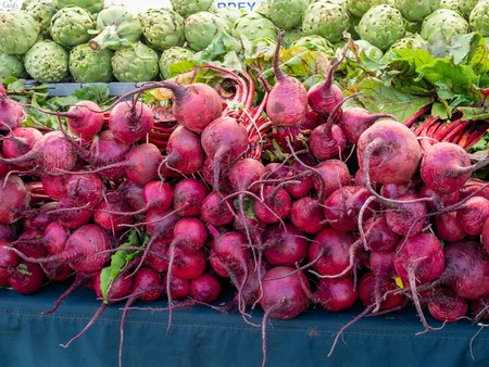 Rows of beets root vegetables sitting on table at farmers market Imagens