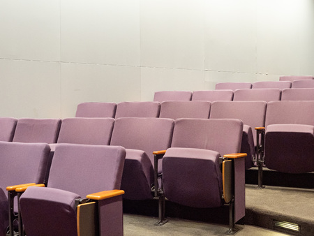 Purple theater style chairs in empty clean small auditorium