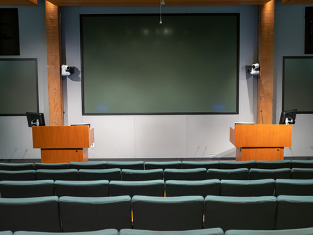 Dimly lit office auditorium with double podiums and multi projector displays Stock Photo