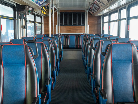 Rows of multiple leather blue empty seats on commuter bus