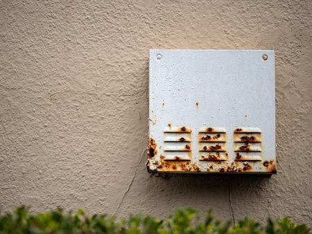 Rusty steel box with vents outside of home near bushes